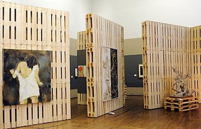 Espositore originale per una galleria d'arte fatta di pallet di legno riciclato