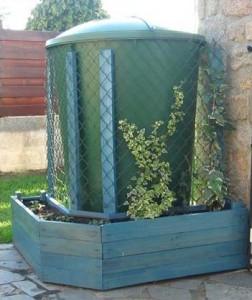Planter fatta di pallet per nascondere un serbatoio d'acqua con piante rampicanti