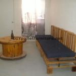 Un divano con pallet e una tavola con una bobina di legno
